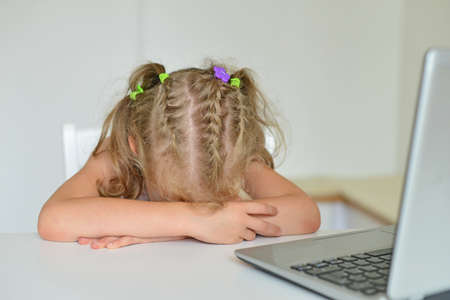 Little girl crying in front of computer at home. photo