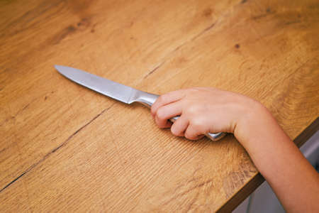 Dangerous situation in the kitchen. Child is trying to get a kitchen knife. photo