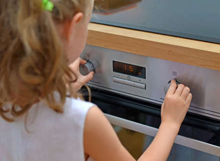 conflagration: Dangerous situation in the kitchen. Child playing with electric oven. Stock Photo