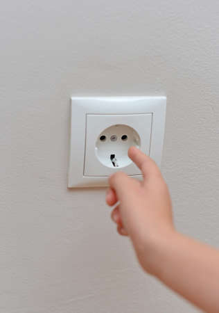 Child sticks his fingers in the socket. Dangerous situation at home. Archivio Fotografico