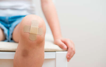 soothe: Child knee with an adhesive bandage and bruise.