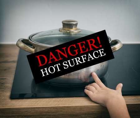 jeopardy: Child touches hot pan on the stove. Dangerous situation at home.  Stock Photo
