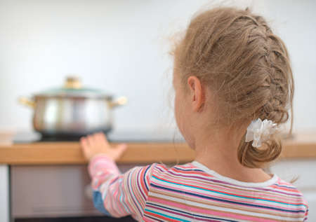 Little girl touches hot pan on the stove. Dangerous situation at home.  Stock Photo