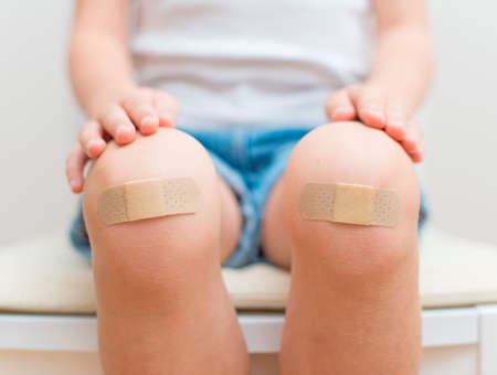 Child knee with an adhesive bandage  Archivio Fotografico