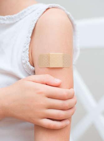 vacuna: Ni�o brazo con un vendaje adhesivo Foto de archivo