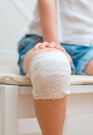 Child knee with adhesive and gauze bandage  photo