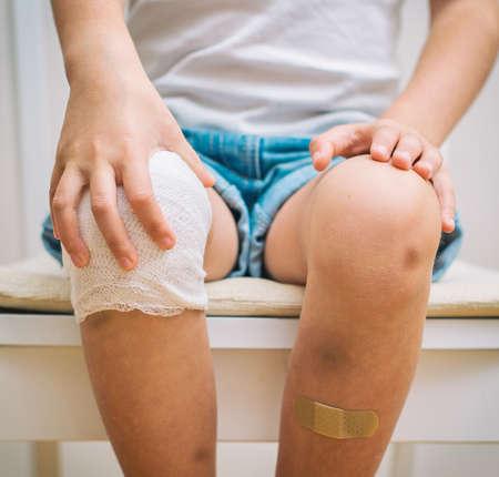 bruise: Child knee with adhesive bandage, bruise and gauze bandage