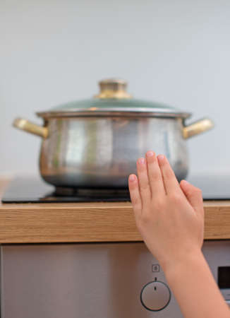 Child touches hot pan on the stove. Dangerous situation at home