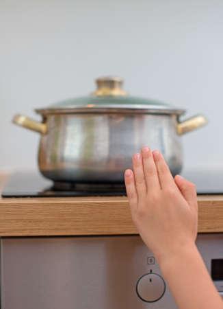peligro: El ni�o toca sart�n caliente en la estufa. Situaci�n peligrosa en casa