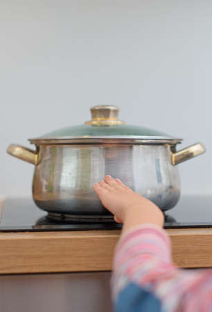 Child touches hot pan on the stove.  Dangerous situation at home Reklamní fotografie - 30980687