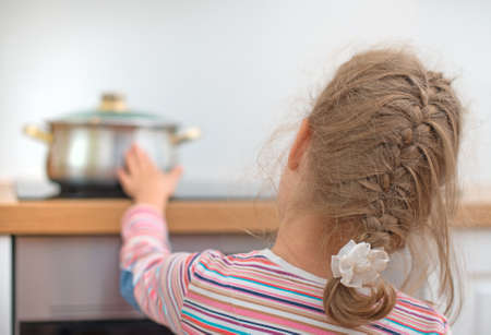 estufa: Niña toca sartén caliente en la estufa. Situación peligrosa en casa