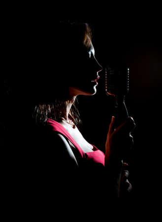 ビンテージ マイクに向かって歌っている女性のシルエット。