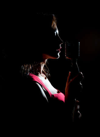Silhouette of woman singing into vintage microphone. Stock Photo