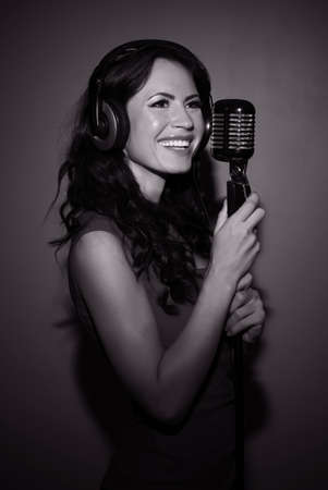 Attractive brunette woman recording a song in music studio. Black and white photo. photo
