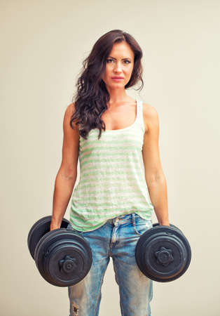 Attractive brunette woman working out with dumbbells. photo