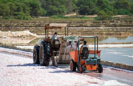 evaporation: Sea salt production. Salt evaporation pond with tractor. Stock Photo