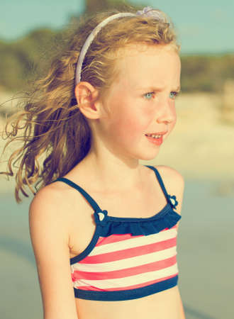 Portrait of little girl on the beach. Vintage effect. photo