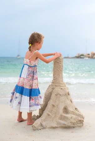 sandcastles: Little girl with sand castle on the beach.