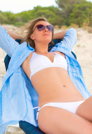 Young woman sunbathing on a lounger. photo