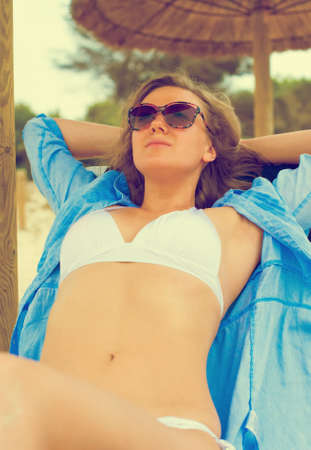 Young woman sunbathing on a lounger. Vintage effect. photo