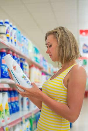 cleaning products: Mujer que elige detergente en polvo en la tienda de comestibles.