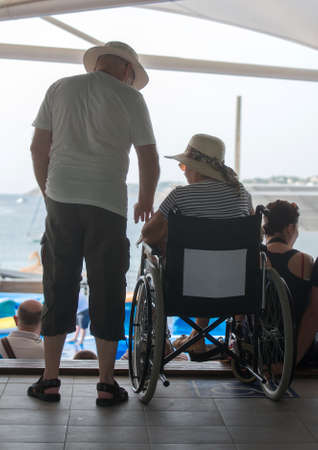 Senior woman on wheelchair with her husband. photo