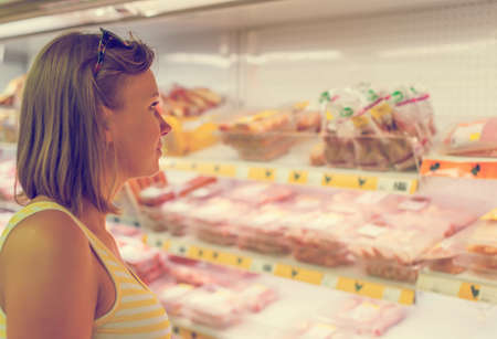 Young woman choosing meat in grocery store. photo