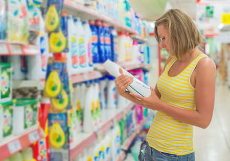 Woman choosing washing powder in grocery store. Banque d'images