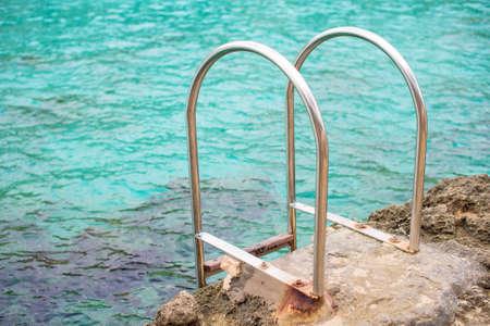 handrails: Handrails mounted on rock near the sea.