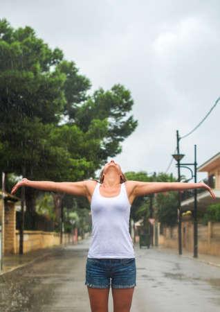 Happy blonde woman enjoying tropical rain. photo