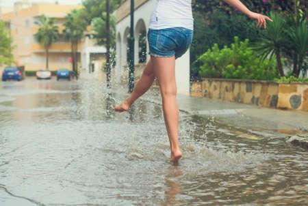 Vrouw met plezier op de straat na de regen. Stockfoto