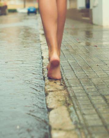 雨の後に通りの楽しい女性。