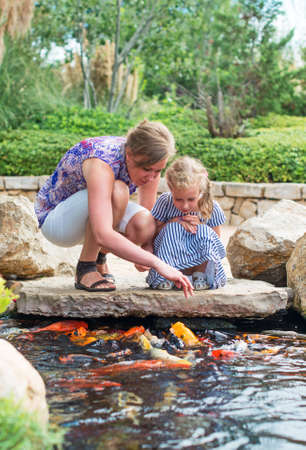 pond: Woman and daughter feeding fishes in pond.