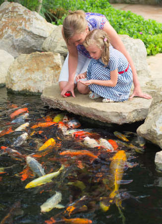 Woman and daughter feeding fishes in pond.