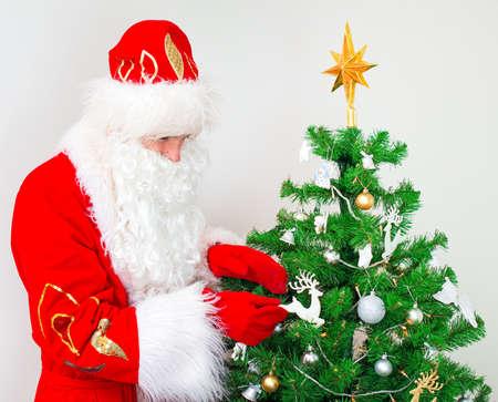 decorates: Santa Claus decorates the Christmas tree.