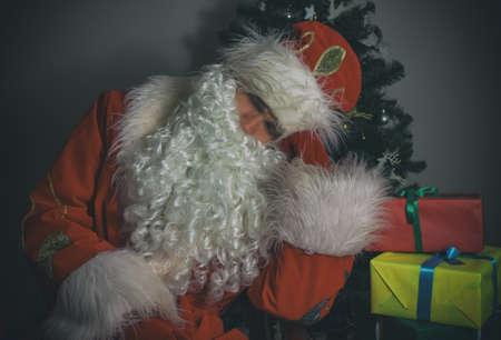 Santa Claus sleeping next to Christmas tree and gifts. photo