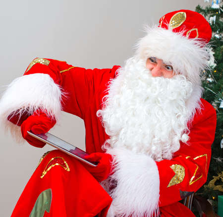 Angry Santa Claus breaks tablet pc. photo