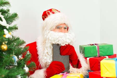 ded moroz: Santa Claus checking wish list at his workshop. Stock Photo