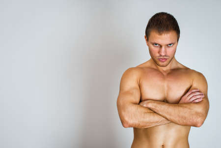 Muscular male model with arms folded. Place for text. photo