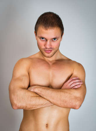 Muscular male model with arms folded. photo