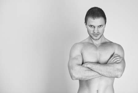 Muscular male model with arms folded. Black and white. Place for text. photo
