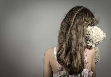 Menina chorando no canto. Conceito de violência doméstica.
