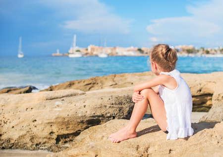 petite fille triste: Sad petite fille assise sur la plage. Place pour le texte. Banque d'images