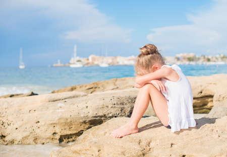 child crying: Niña triste que se sienta en la playa. Lugar para el texto.