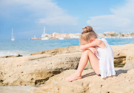 crying child: Sad little girl sitting on the beach. Place for text.