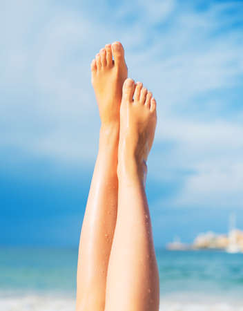 beautiful feet: Close-up view of womens legs on the beach.