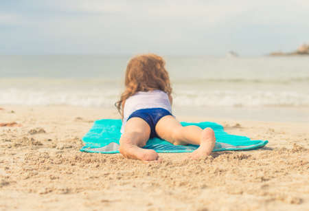 girl with towel: Little girl sunbathing on sand. Place for text.
