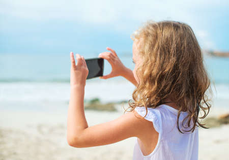 resort beach: Little girl making video or photo with mobile phone.