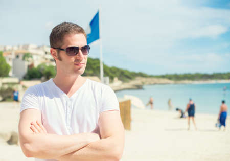 Handsome man in glasses on the beach. photo