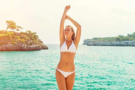 arms raised girl: Young sensual woman posing near the sea.
